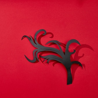 Creative greeting card handcraft from paper in the form of a branch on a red background with reflection of shadows and copy space for text. flat lay