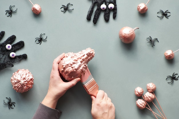 Creative grey and pink paper flat lay with hands painting pumpkin with pink glittering paint. top view with mesh gloves with chocolate eyes, painted pumpkins and decorative spiders.
