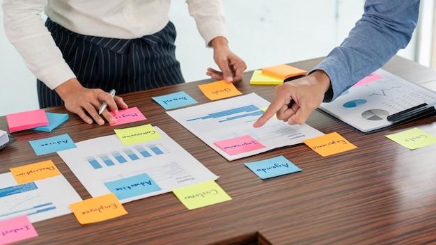 브레인 스토밍하는 비즈니스 사람들의 크리에이티브 그룹은 테이블 결정에 대한 아이디어를 공유하기 위해 스티커 메모를 사용하여 비즈니스 회의실에서 계획을 개발하기위한 개념을 선택합니다.