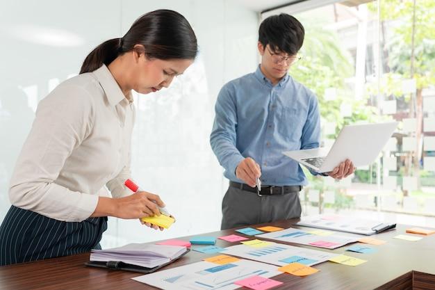 ブレーンストーミングを行うビジネスマンのクリエイティブグループは、付箋紙のピッキングを使用して、テーブルの決定に関するアイデアを共有します