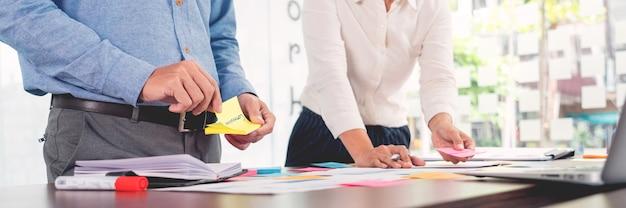 ブレーンストーミングを行うビジネスマンのクリエイティブグループは、付箋紙を使ってテーブルでアイデアを共有します