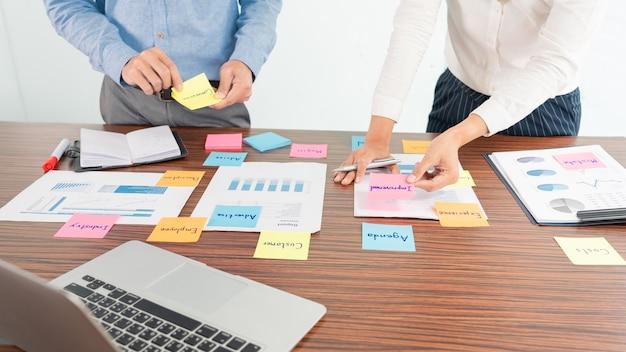 브레인 스토밍하는 사업 사람들의 창조적 인 그룹은 테이블에 대한 아이디어를 공유하기 위해 선택하는 스티커 메모를 사용합니다.