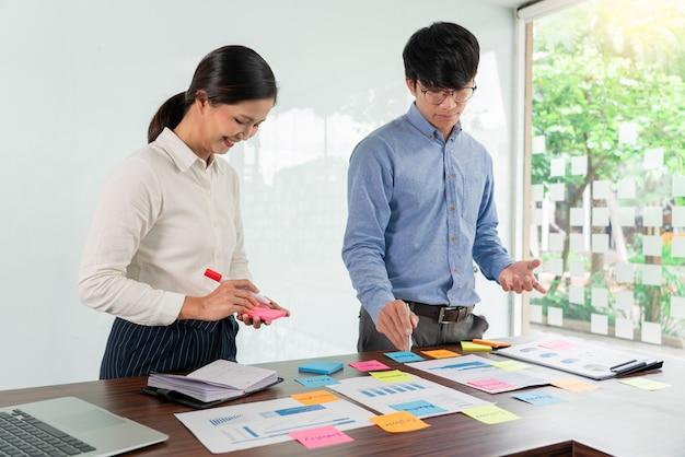 브레인 스토밍하는 사업 사람들의 크리에이티브 그룹은 아이디어를 공유하기 위해 선택하는 스티커 메모를 사용합니다.