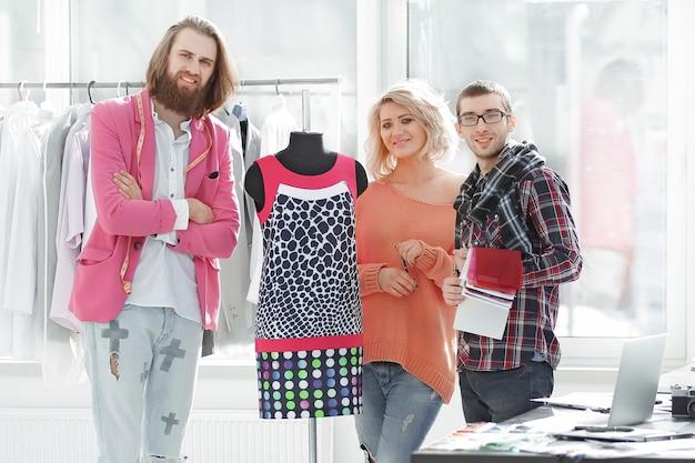 Творческая группа дизайнеров, стоящих в современной студии. фото с копией пространства