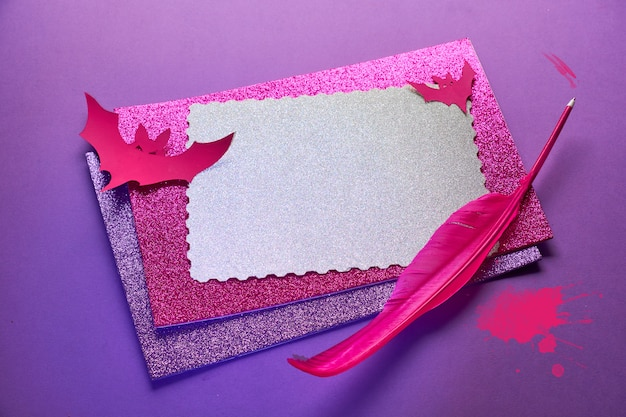 Creative halloween background in glowing neon pink and purple with stack of glittering paper, quill and paper bats. space for your text on the top card.