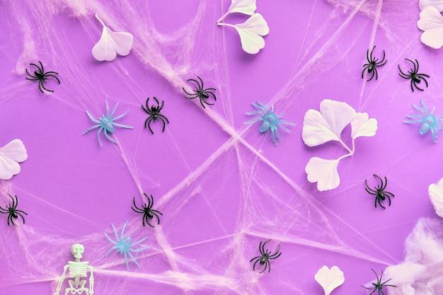 鮮やかな紫色のネオン紙に白いイチョウの葉、クモの巣、黒いクモと創造的なハロウィーンの背景。フラット横たわっていた、トップビュー、トレンディな背景。