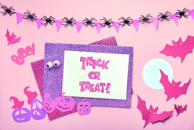 創造的なハロウィーンフラットレイアウトコピースペースとピンクの紙の背景。 「トリックオアトリート」のテキストと紙の装飾が施されたカード。フラグとクモの装飾的な花輪。