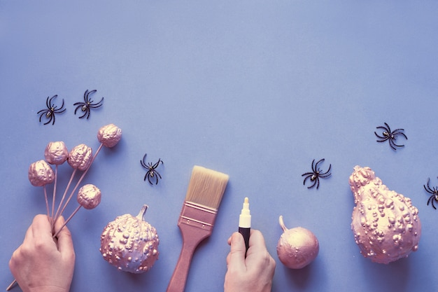 Creative halloween flat lay on grey paper on light purple wall with copy-space. female hands holding marker and small painted pumpkins, plastic spiders and paint brush.