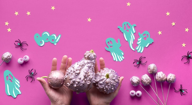Creative halloween flat lay on purple paper background with paper ghosts, stars and chocolate eyes. hands in black mesh gloves