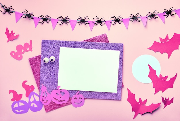 Творческий хэллоуин плоский лежал стол на розовой бумаге с копией пространства. пустые карты и бумажные украшения: летучие мыши и фонарь