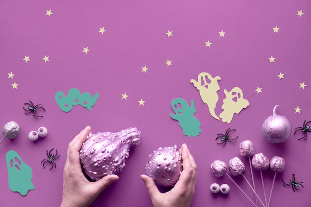 Creative halloween flat lay on vibrant pink paper wall with paper ghosts, stars and chocolate eyes. hands in black gloves holding pumpkins painted gilded pink.