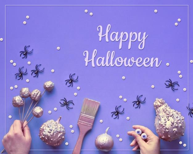 Творческий хэллоуин неоновые плоские лежал на фиолетовой бумаге, текст «happy halloween». тыквы окрашены в розовый цвет металлик, руки, кисть, рука монстра с шоколадными глазами.