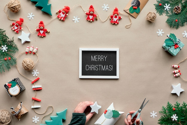 Creative handmade decor, zero waste christmas frame. textile trinkets, hands. eco friendly flat lay, text merry xmas