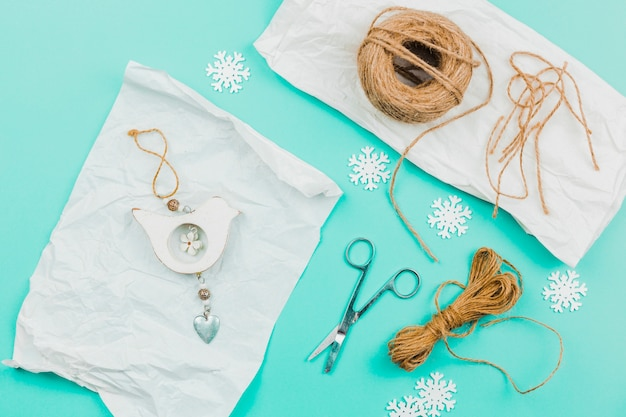 Creative handmade wall hanging on parchment paper with snowflake; scissor and jute thread on turquoise backdrop