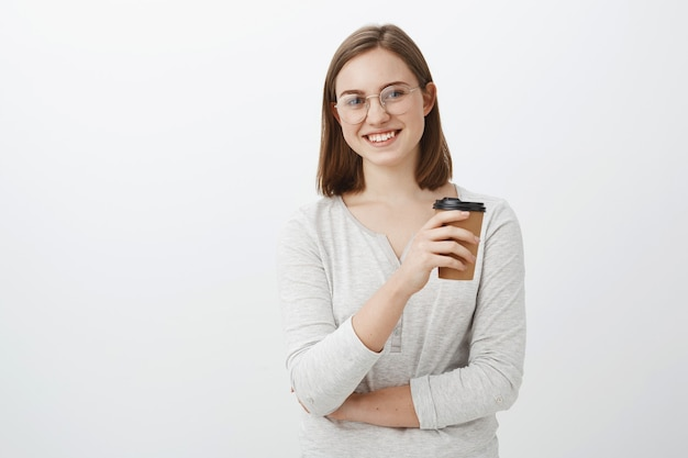 Творческая счастливая и энергичная привлекательная молодая женщина в очках держит бумажный стаканчик, пьет кофе и посмеивается, весело и забавно разговаривая во время обеда на работе над серой стеной