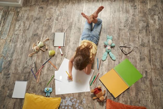 Творческие хобби для детей вид сверху маленькой кавказской девочки, лежащей на деревянном полу дома и