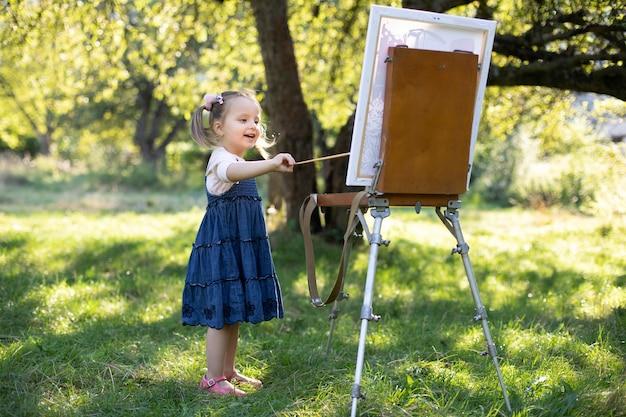 Творческое хобби и досуг. маленькая талантливая девочка дошкольного возраста художника, развлекаясь, рисуя картину на мольберте на открытом воздухе на природе в солнечном саду в яркий летний день.
