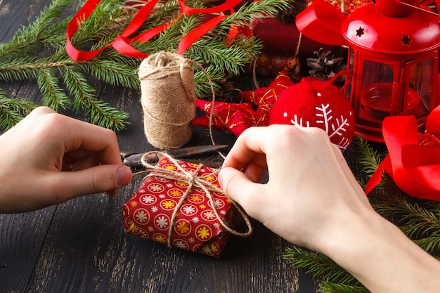 Creative hobby. hands wrap christmas holiday handmade present in craft paper with twine ribbon