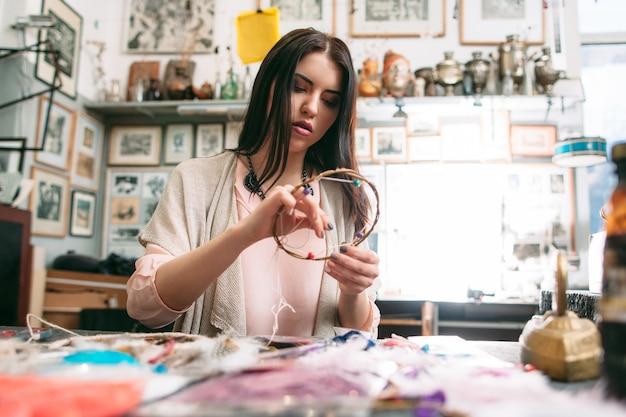 Creative hobby. woman making dreamcatcher in art studio