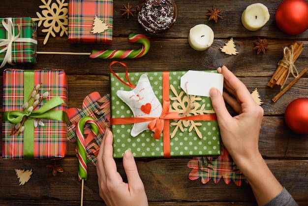 クリエイティブな趣味。女性の手は赤いリボンで紙にクリスマス休暇の手作りプレゼントを包みます。暗い木製のテーブル、上面図に雪の結晶で飾られたクリスマスギフトボックスを持参してください。
