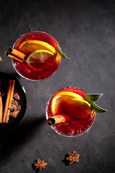 Креативный праздничный коктейль с напитком в геометрическом стакане на черном фоне