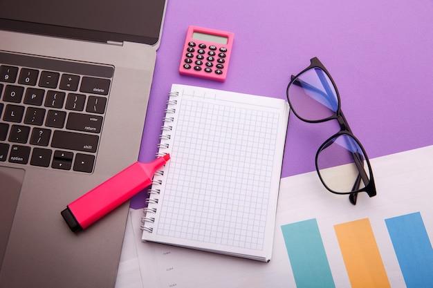 電卓、ラップトップ、ノートブックを備えたクリエイティブな家庭の職場。在宅勤務のコンセプト。