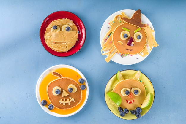 Creative homemade halloween pancakes for breakfast, in form of funny monsters, ghost, bat, witch. with traditional trick or treat sweets, candy and decorations, top view on colorful blue background
