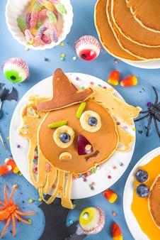 面白いモンスター、幽霊、コウモリ、魔女の形で、朝食用の創造的な自家製ハロウィーンのパンケーキ。伝統的なトリックオアトリートのお菓子、キャンディー、装飾品、カラフルな青い背景の上面図