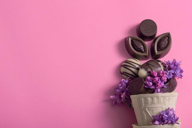 Творческое мороженое шоколадные конфеты в вафельном стаканчике, украшенном сиренью на цветном фоне. день шоколада