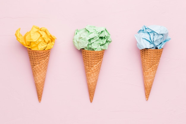 Creative ice cream from crumpled colorful paper in waffle cones