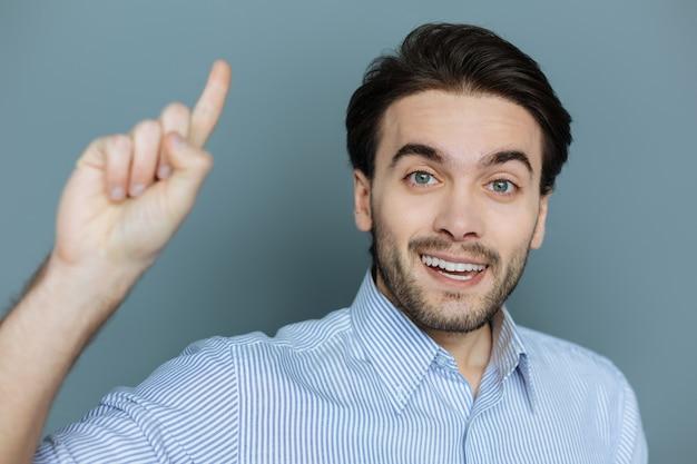 創造的なアイデア。問題の解決策を見つけながら、笑顔で指で上を向いている陽気な気持ちの良い賢い男