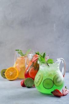 創造的なアイデア。組成。フルーツを添えたガラスデカンターのさまざまな色のレモネードと、テーブルの上に新鮮なミントとスライスしたフルーツを添えて。