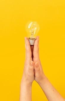 여자 손에 전구와 창의적인 아이디어 개념 배경