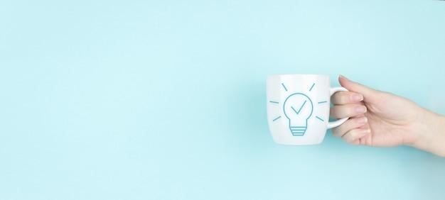 창의적인 아이디어입니다. 아이디어와 혁신의 개념입니다. 소녀는 파란색 배경에 기호 전구 아이콘이 있는 모닝 커피 컵을 잡고 있습니다. 솔루션 분석 및 개발, 혁신적인 기술.
