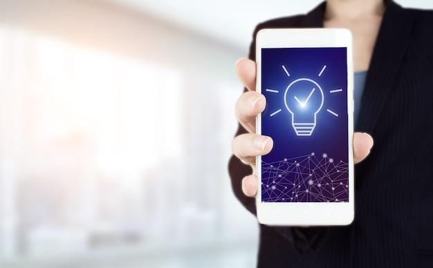 創造的なアイデア。アイデアと革新の概念。明るいぼやけた背景にデジタルホログラム電球サイン付きの白いスマートフォンを手に持ってください。起業または成功への目標。