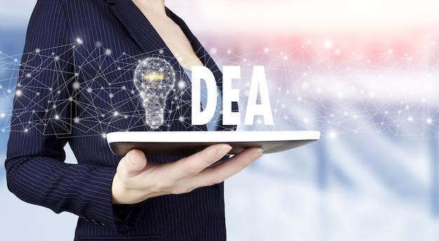 創造的なアイデア。アイデアと革新の概念。明るいぼやけた背景にデジタルホログラム電球のサインと白いタブレットを手に持ってください。