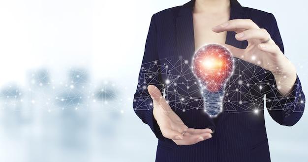 創造的なアイデア。アイデアと革新の概念。明るい背景のぼやけた仮想ホログラフィック電球アイコンを持っている両手。電球とのネットワークの明るいアイデア