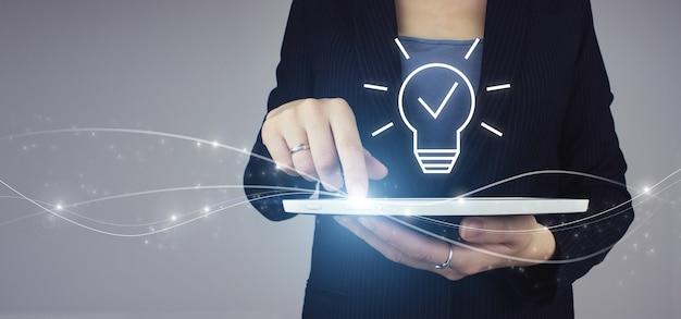 창의적인 아이디어입니다. 아이디어와 혁신의 개념입니다. 회색 배경에 디지털 홀로그램 전구 기호가 있는 사업가 손에 있는 흰색 태블릿. 솔루션 분석 및 개발, 혁신적인 기술.