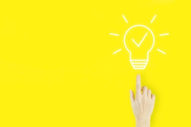 창의적인 아이디어입니다. 아이디어와 혁신의 개념입니다. 노란색 배경에 전구 홀로그램으로 가리키는 젊은 여성의 손 손가락. 사업 시작 또는 성공 목표.