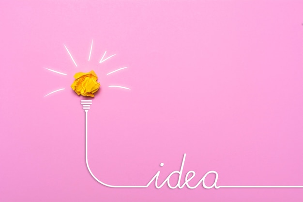 Creative idea of crumpled paper. a burning light bulb on a pink background. education concept.