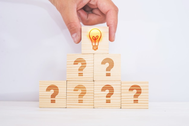 Creative idea and innovation concept. matched wooden cube block with a light bulb icon on top of a pyramid and a question mark symbol