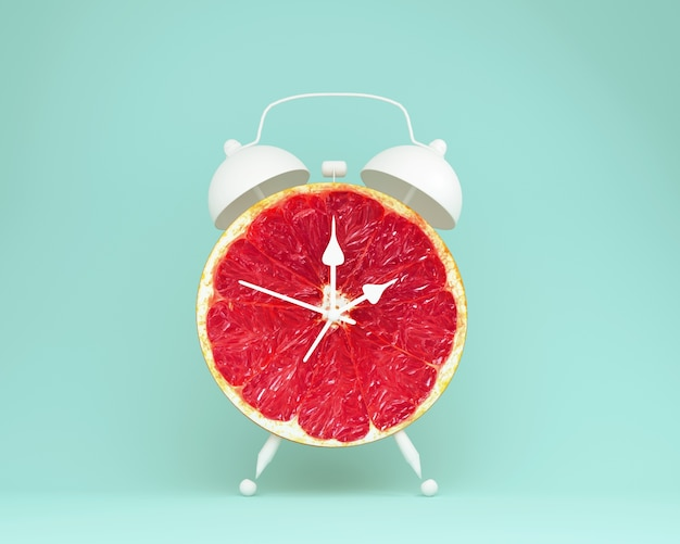 Creative idea layout fresh grapefruit slice alarm clock on blue background. minimal fruit