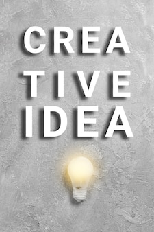 Creative idea text with glowing light bulb on gray background minimal art poster