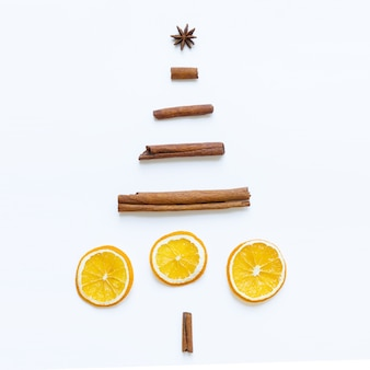 Creative image of handmade christmas tree made of anise star, cinnamon sticks, dried orange slices on white surface. new year concept. flat lay.