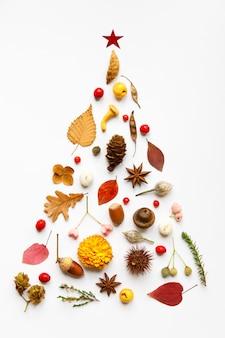 야생 딸기, 마른 잎과 꽃, 아니스, 견과류, 버섯, 가시 밤나무, 콘, 흰색 표면에 나뭇 가지로 만든 수제 크리스마스 트리의 크리에이티브 이미지. 새해 개념. 평평하다.