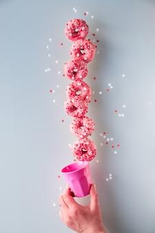 Творческий образ идеального баланса, башни или пирамиды вкусных розовых пончиков, балансирующих на нижнем пончике, удерживаемом женской рукой концептуальное равновесие на сером фоне.
