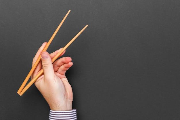 Творческий образ деревянных палочек для еды в мужских руках на черном фоне