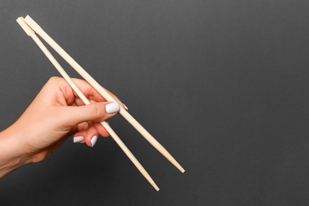 Creative image of wooden chopsticks in female hand on black background. japanese and chinese food with copy space.