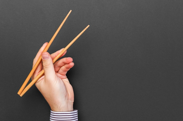 Creative image of wooden chopsticks in male hands on black background