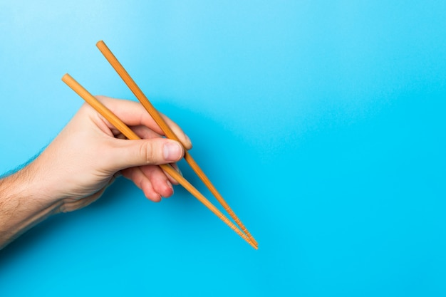 Creative image of wooden chopsticks in male hands on blue background. japanese and chinese food with copy space